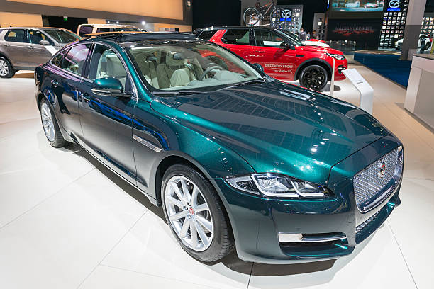 Jaguar XJ luxury saloon car Brussels, Belgium - Januari 12, 2016: Green Jaguar XJ luxury saloon car front view. The car is on display during the 2016 Brussels Motor Show. The car is displayed on a motor show stand, with lights reflecting off of the body. There are people looking around and other cars on display in the background. jaguar xj stock pictures, royalty-free photos & images