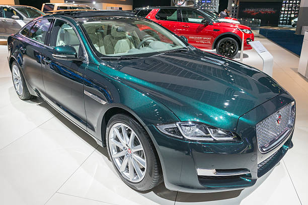 Jaguar XJ luxury saloon car Brussels, Belgium - Januari 12, 2016: Green Jaguar XJ luxury saloon car front view. The XJ is the flagship model of Jaguar Cars and is available in both standard and long-wheelbase form, as well as many special editions. The car is on display during the 2016 Brussels Motor Show. The car is displayed on a motor show stand, with lights reflecting off of the body. There are people looking around and other cars on display in the background. jaguar xj stock pictures, royalty-free photos & images