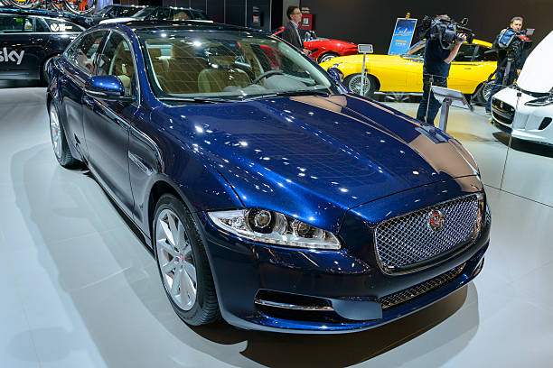 Jaguar XJ Brussels, Belgium - January 14, 2014: Blue Jaguar XJ series luxury saloon car on display at the 2014 Brussels motor show. People in the background are looking at the cars. jaguar xj stock pictures, royalty-free photos & images