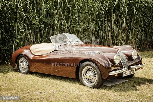 Jüchen, Germany - August 5, 2016: Jaguar XK120 Roadster classic British Sports car. The Jaguar XK120 was manufactured by Jaguar between 1948 and 1954 The car is on display during the 2016 Classic Days at castle Dyck. The car is displayed in a field.