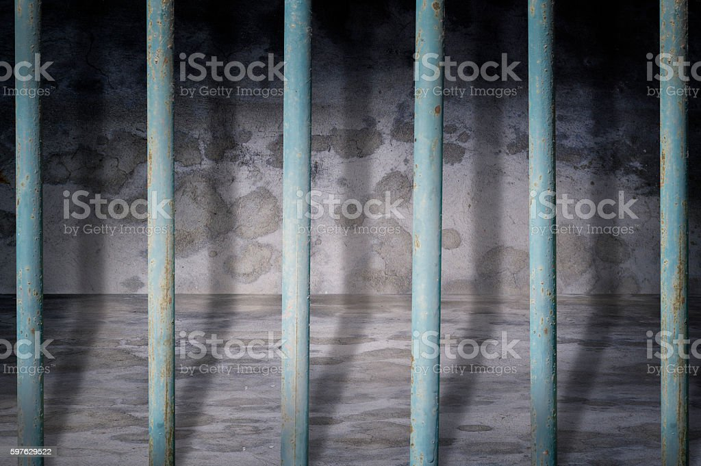Jail cells iron bars casting shadows on the prison floor stock photo