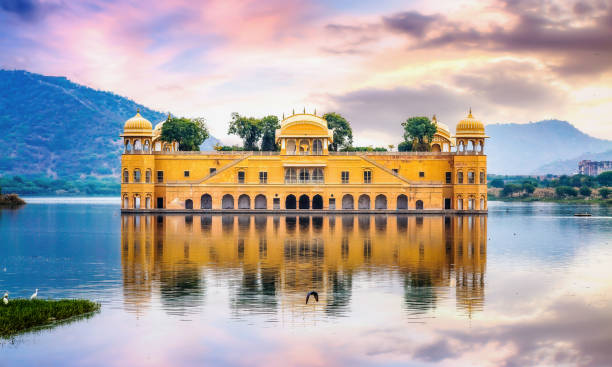Jal Mahal water palace Jaipur Rajasthan with landscape at sunset. Jal Mahal water palace Jaipur Rajasthan at sunset with vibrant moody sky udaipur stock pictures, royalty-free photos & images