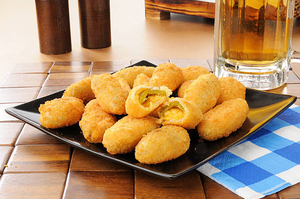 Jalapeno and cheddar cheese poppers Jalapeno and cheddar cheese poppers with a mug of beer jalapeno pepper stock pictures, royalty-free photos & images