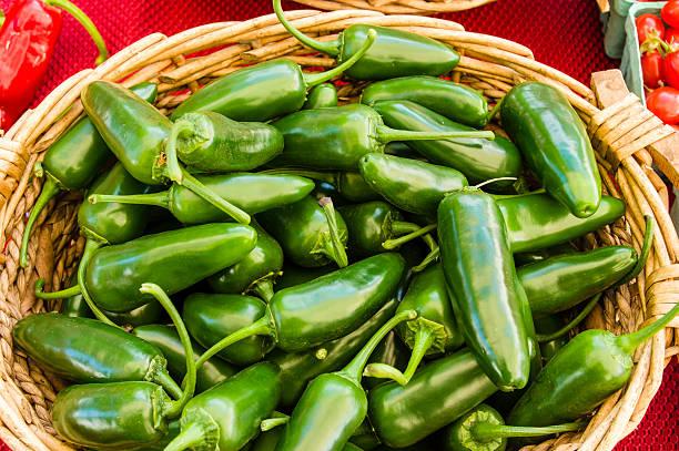 Jalpeno peppers in wicker basket display stock photo