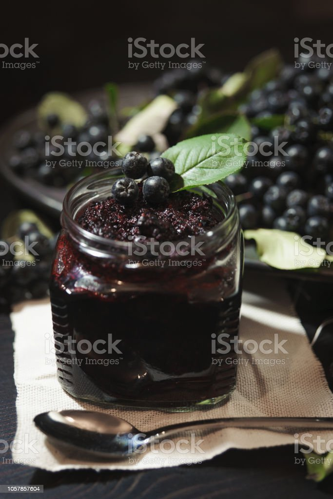 Jam from black chokeberries ( Aronia melanocarpa ) and its berries on dark table. Homemade preserves. – zdjęcie
