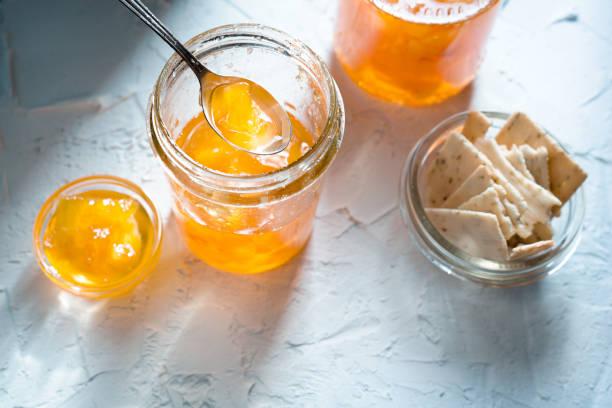 marmelade aus ananas in gläsern auf einem weißen hintergrund und cookies - ananas marmelade stock-fotos und bilder