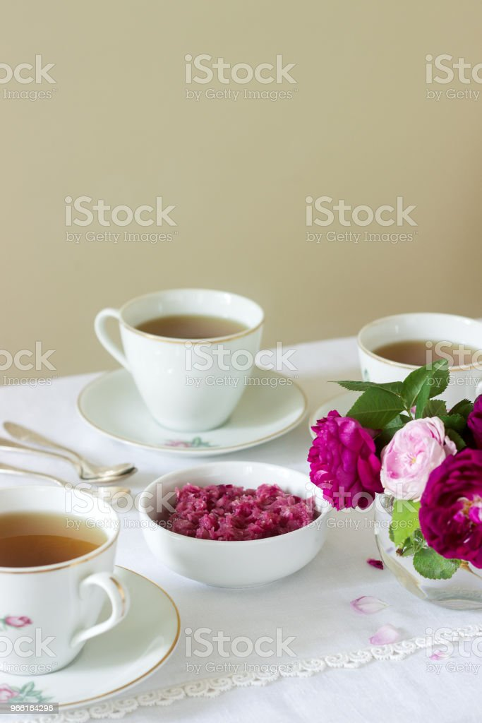 Jam from the petals of the Damascus rose, a cup of green tea and a vase of roses on a light table. Rustic style. - Royalty-free Aromatherapy Stock Photo