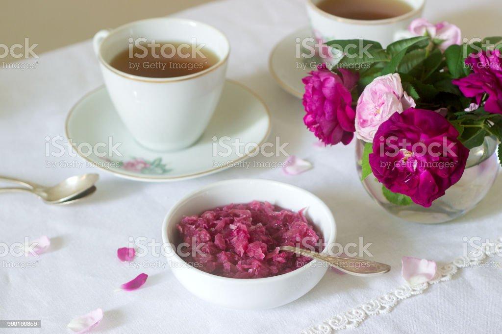 Jam från kronblad av ros i Damaskus, en kopp grönt te och en vas med rosor på ett ljusbord. Rustik stil. - Royaltyfri Alla hjärtans dag Bildbanksbilder