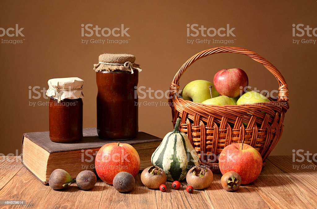 Jam into jars, books, and fruits in wicker basket stock photo