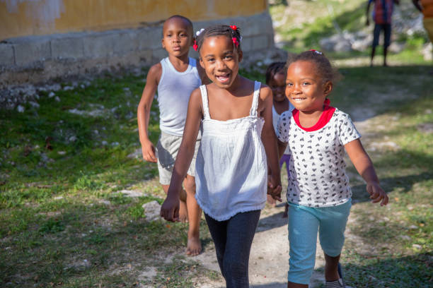 Jamaican children playing outside in poor village stock photo