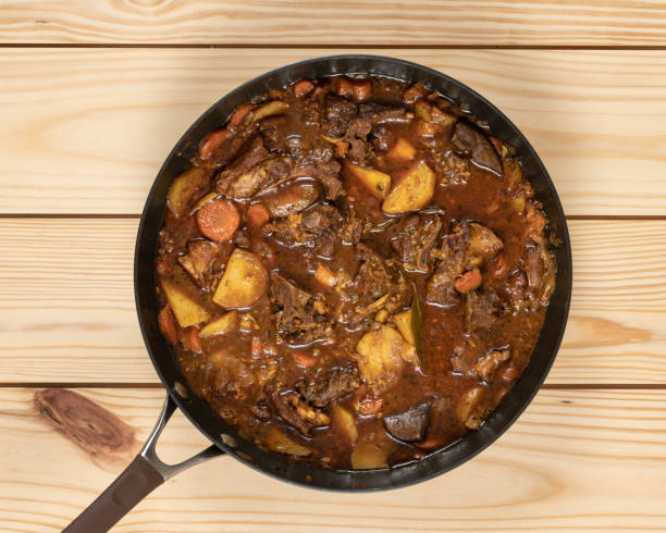 Jamaican Goat Curry Close-up of colorful goat stew in cooking pan on top of  wooden table. stew stock pictures, royalty-free photos & images