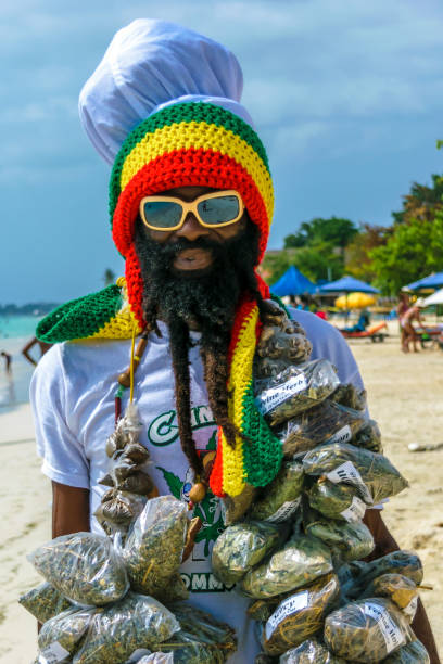 Jamaican Rastafarian man Negril, Jamaica - July 13 2014: Jamaican Rastafarian man selling herbs on the beach in Negril. rastafarian stock pictures, royalty-free photos & images