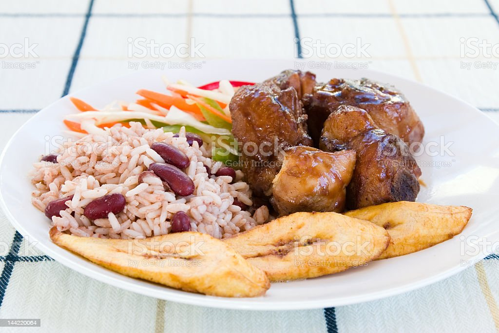 Jamaican style chicken with rice and beans and vegetables stock photo