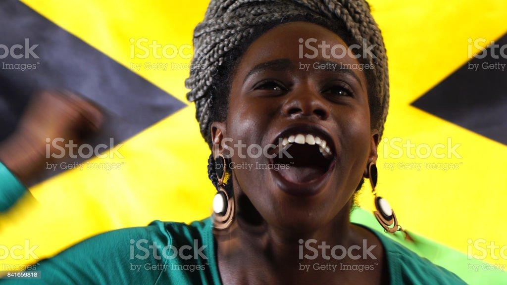Jovem jamaicano preto mulher comemorando com bandeira Jamaica - foto de acervo
