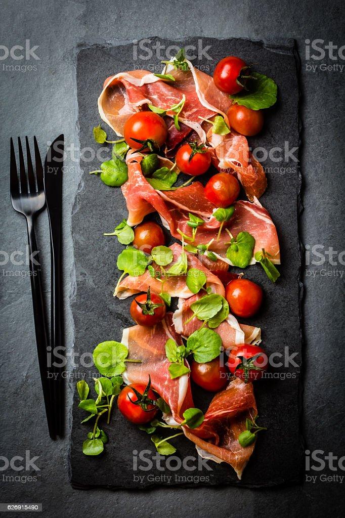 Jamon serrano, tomatoes, arugula salad, black stone slate board stock photo