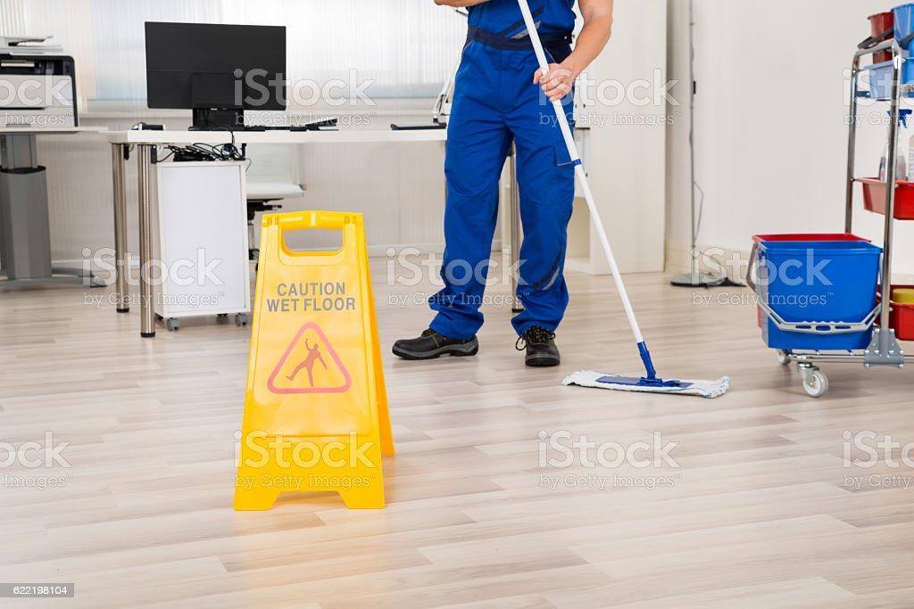 Janitor Cleaning Floor With Mop In Office stock photo