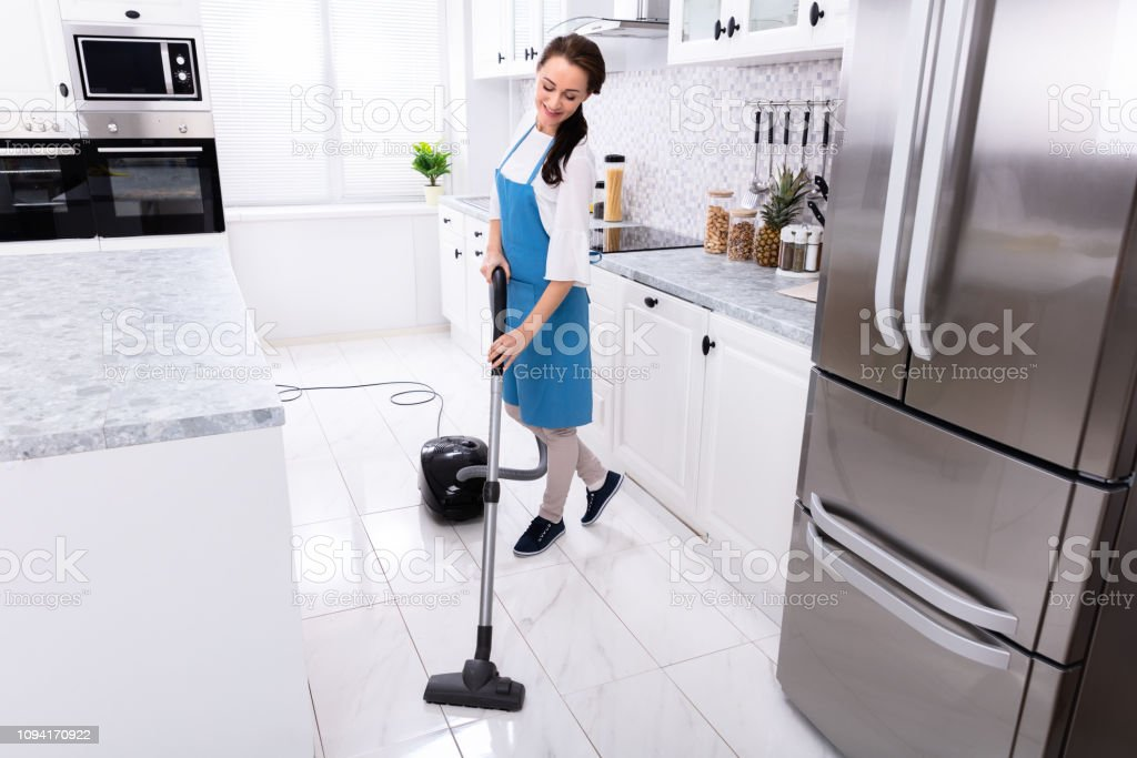 Young Female Janitor In Uniform Cleaning Kitchen Floor With Vacuum...