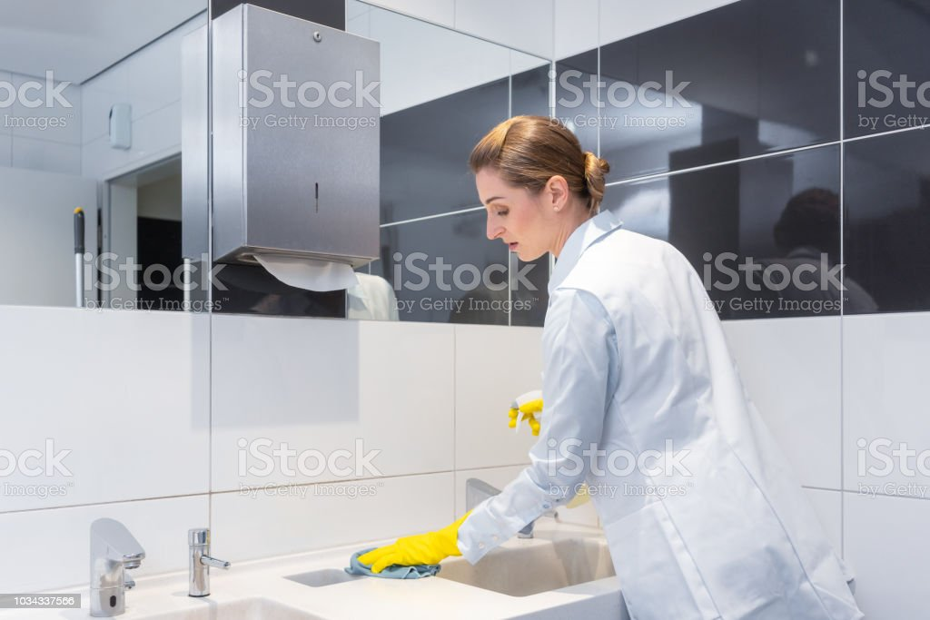 Janitor cleaning sink in public washroom stock photo