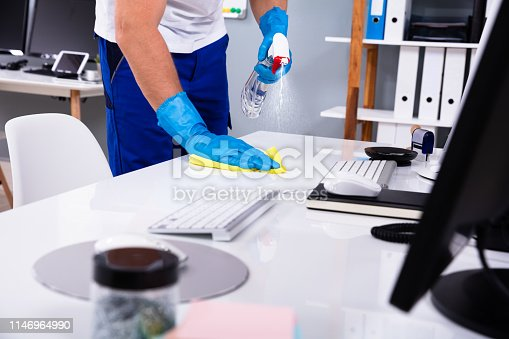 Janitor cleaning white desk in modern office