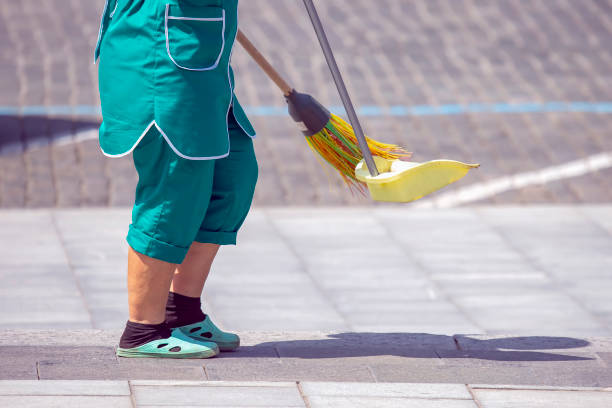 janitor cleans the sidewalk of the city stock photo