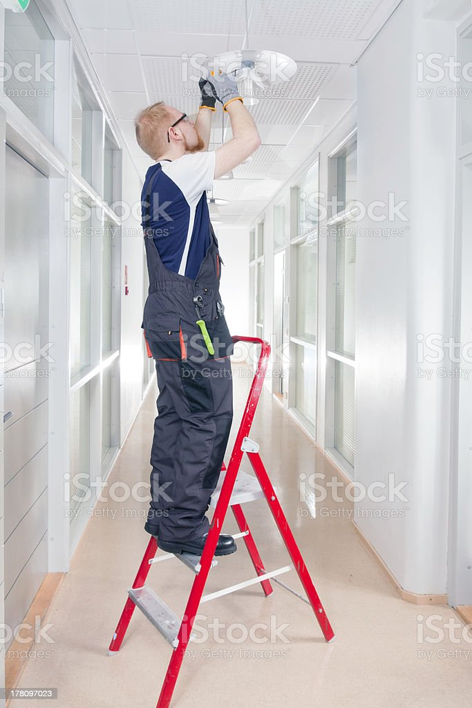 Janitor Fixing Broken Lamp stock photo