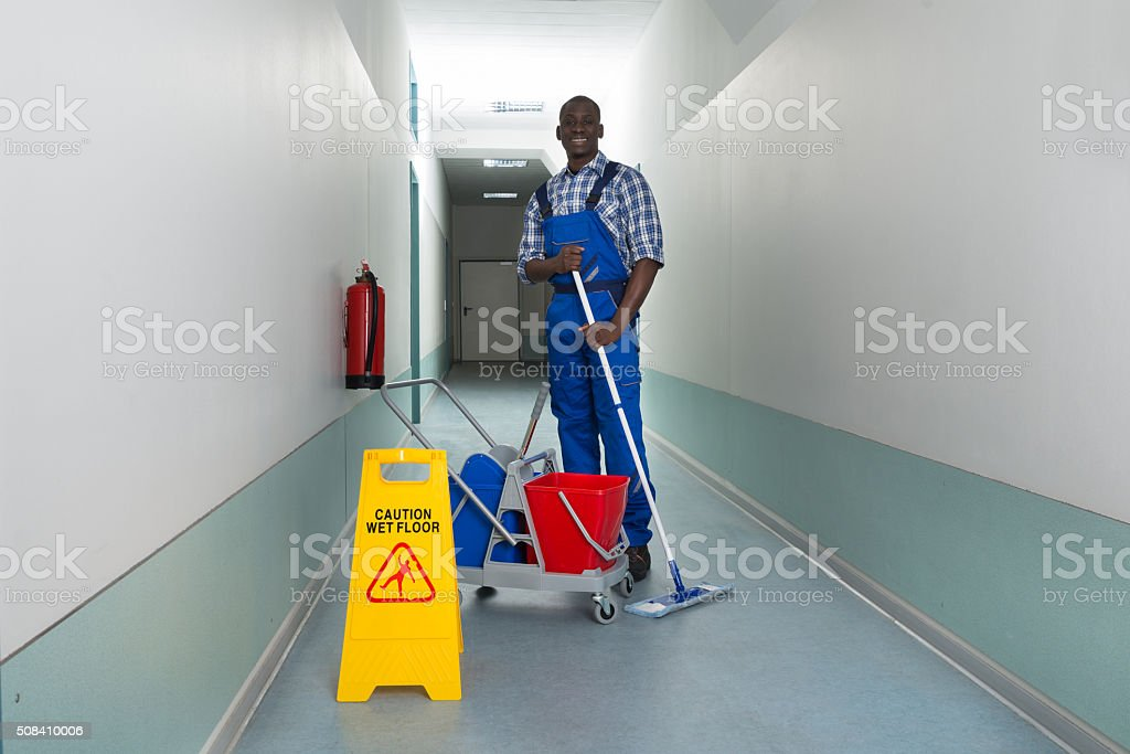 Janitor Holding Mop With Bucket And Wet Floor Sign stock photo