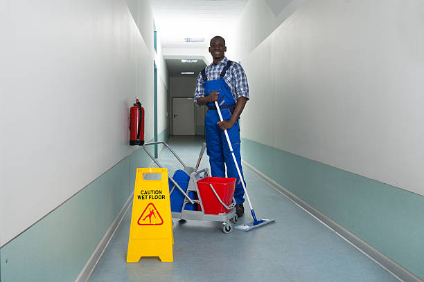 janitor holding mop with bucket and wet floor sign - custodian stock pictures, royalty-free photos & images