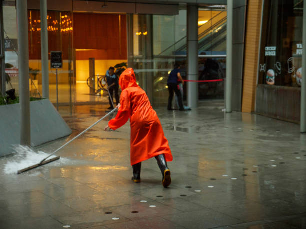 Janitor in raincoat wipes water from floor, Bangkok, Thailand stock photo