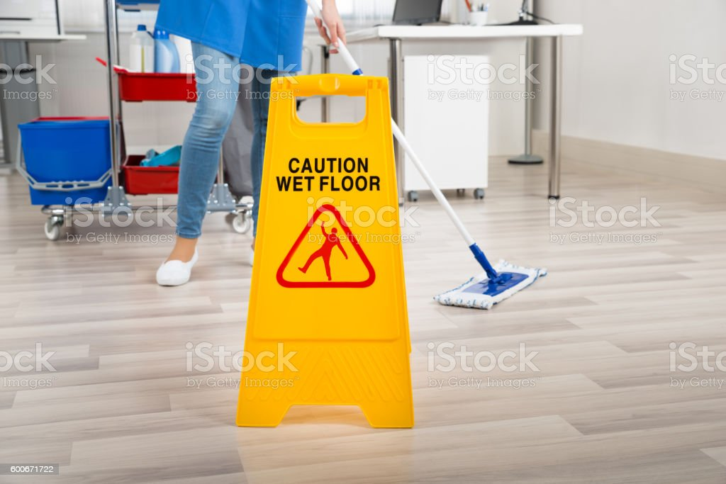 Janitor Mopping Floor By Wet Caution Sign In Office stock photo