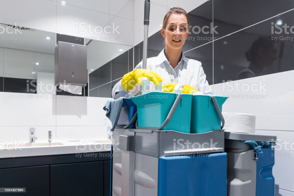 Janitor or charlady with her work tools looking at camera in toilet stock photo