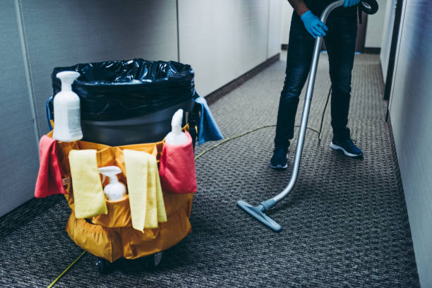 Janitor vacuum cleaning the corridor of an office building. stock photo