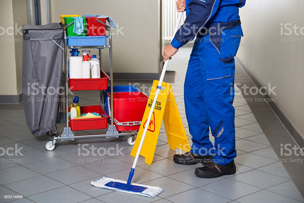 Janitor With Broom Cleaning Office Corridor stock photo
