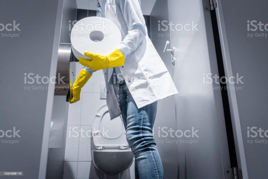Janitor woman changing paper in public toilet stock photo