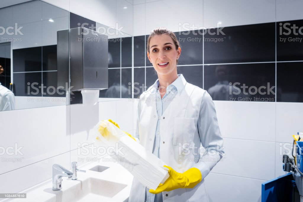 Janitor woman changing paper towels in public restroom stock photo