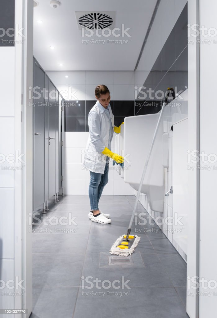 Janitor woman cleaning urinals in public toilet stock photo