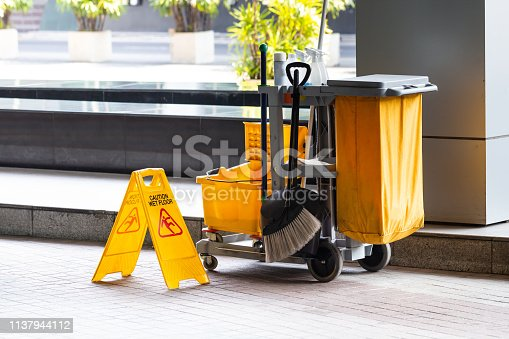 Janitorial and mop bucket on cleaning with caution wet floor sign.