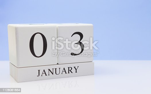 1027407218istockphoto January 03st. Day 03 of month, daily calendar on white table with reflection, with light blue background. Winter time, empty space for text 1128081854