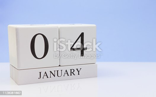 1027407218istockphoto January 04st. Day 04 of month, daily calendar on white table with reflection, with light blue background. Winter time, empty space for text 1128081862