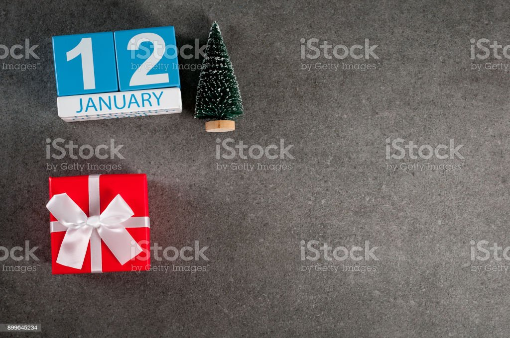 January 12th. Image 12 day of January month, calendar with x-mas gift and christmas tree. New year background with empty space for text, mockup stock photo
