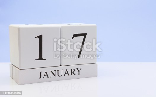 1027407218 istock photo January 17st. Day 17 of month, daily calendar on white table with reflection, with light blue background. Winter time, empty space for text 1128081986