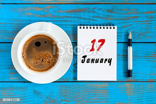 istock January 17th. Day 17 of january month, calendar on blue wooden office workplace background. Winter at work concept 905841238