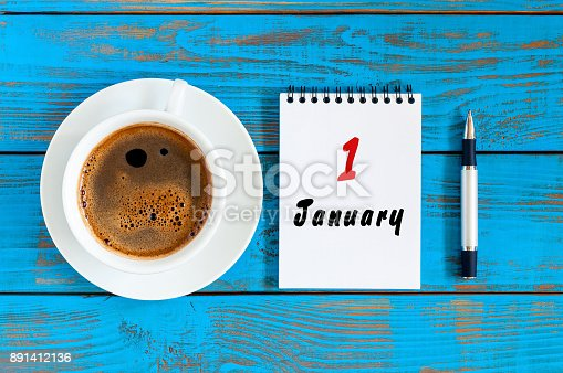 istock January 1st. Day 1 of january month, calendar on blue wooden office workplace background. Winter at work concept 891412136