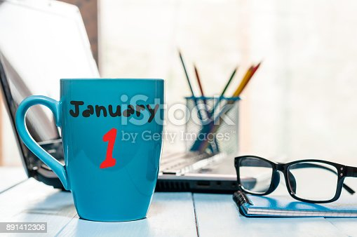 istock January 1st. Day 1 of month, Calendar on cup morning coffee or tea, teacher workplace background. Winter time. Empty space for text 891412306