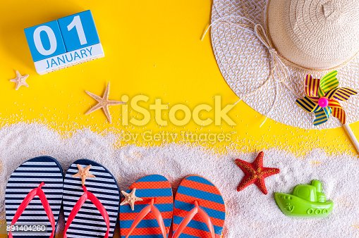 945046208 istock photo January 1st. Image of january 1 calendar with summer beach accessories and traveler outfit on background. Winter like Summer vacation concept 891404260