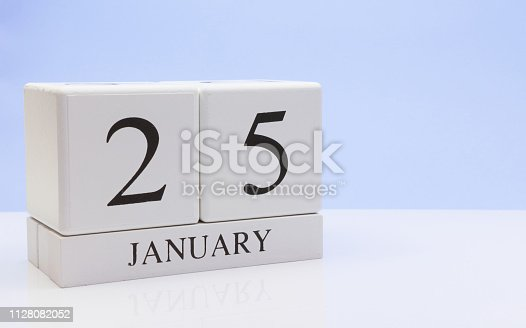 1027407218istockphoto January 25st. Day 25 of month, daily calendar on white table with reflection, with light blue background. Winter time, empty space for text 1128082052