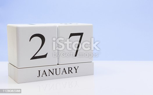 1027407218istockphoto January 27st. Day 27 of month, daily calendar on white table with reflection, with light blue background. Winter time, empty space for text 1128082088