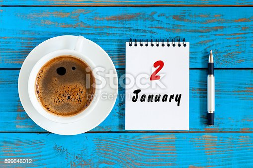 istock January 2nd. Day 2 of january month, calendar on blue wooden office workplace background. Winter at work concept 899646012