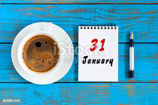 istock January 31st. Day 31 of month, calendar on blue wooden office workplace background. Winter at work concept 908881340