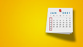 2021 January calendar on a white note paper pinned on wall against yellow background. High resolution and copy space for all your crop needs.