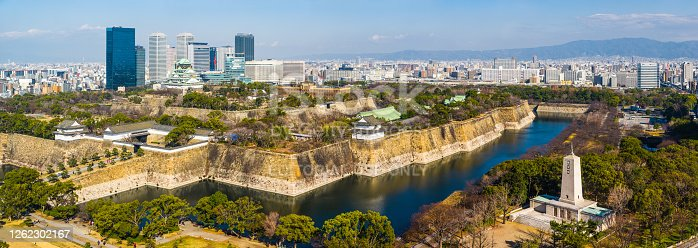 The iconic five storey tower of Osaka Castle surrounded by the leafy foliage of Osaka Castle Park and overlooked by the modern skyscrapers of downtown Osaka, Japan's vibrant second city.